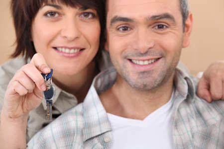 Mature couple holding up a set of keys photo