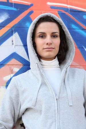 hooded sweatshirt: Woman in a hooded sweatshirt standing in front of graffiti