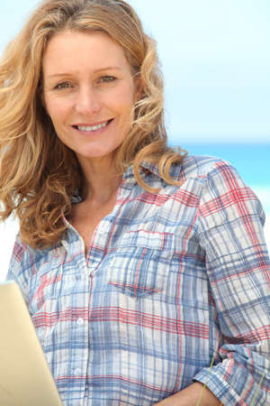 woman 40 years: Woman smiling on laptop. Stock Photo