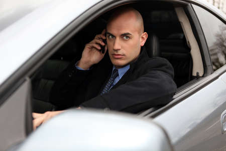 distraction: Bald businessman making call from car Stock Photo