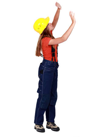 studio happy overall: A female construction worker checking the walls.
