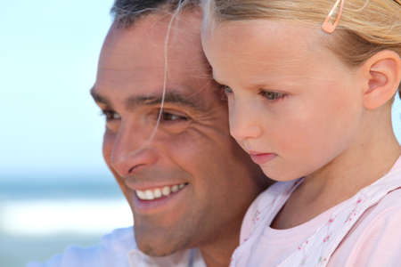 Father with young daughter by the ocean photo