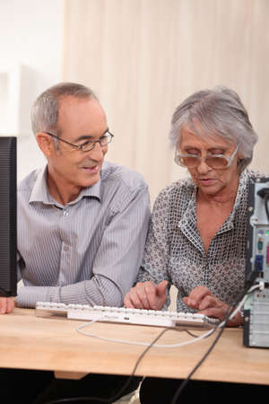 70 year old man: Elderly couple learning computer skills Stock Photo