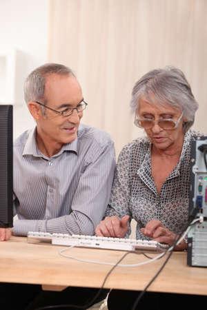 65 70 years: Elderly couple learning computer skills Stock Photo