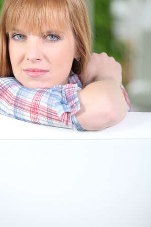 leaning by barrier: Woman resting her head and arm against a fence Stock Photo