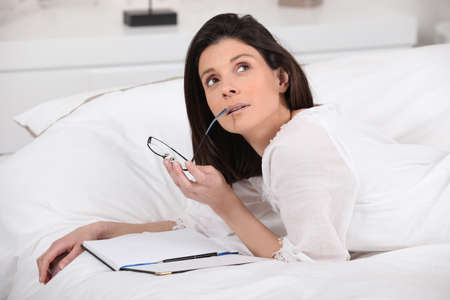 writers block: Thoughtful woman writing in bed Stock Photo