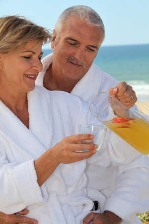 50 55: Couple having a glass of juice by the seaside