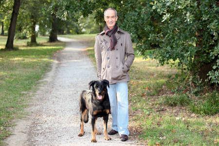 Senior man walking his dog in the woods photo
