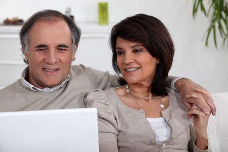 old technology: coppia matura seduta sul divano con il portatile Archivio Fotografico