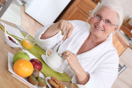 65 70: Elderly woman having breakfast Stock Photo