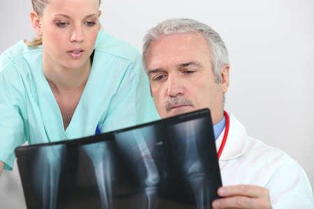 de rodillas: Médico y la enfermera mirando una radiografía pierna Foto de archivo