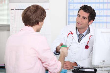 Patient handing card to doctor photo