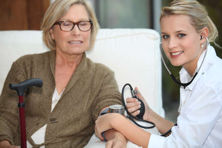 A doctor taking her patient blood pressure. photo