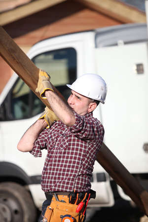 Construction worker carrying a heavy plank photo