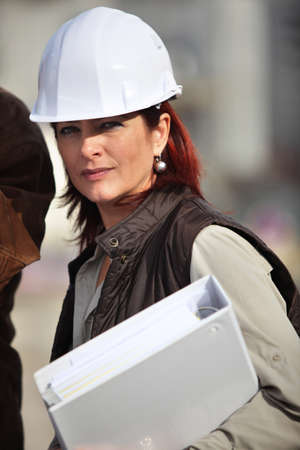 woman hard working: An engineer holding a binder and wearing a safety hat