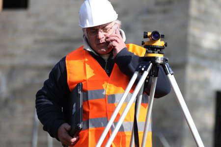 tripod mounted: Man surveying site Stock Photo