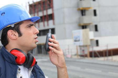 two way: Man speaking into a walkie-talkie