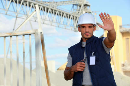 cautious: worker on a construction site waving his hand