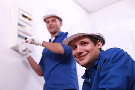 electricista: Electricistas jóvenes con una caja de fusibles