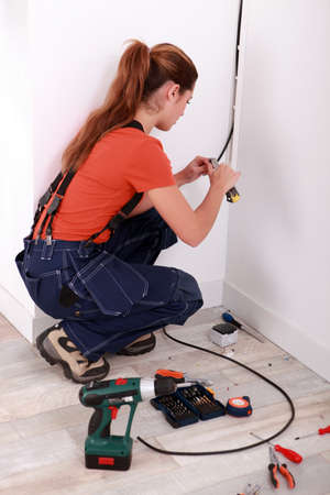 workwoman: Electrician installing electrical wiring