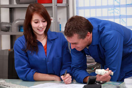 coverall: Workers writing on a desk Stock Photo