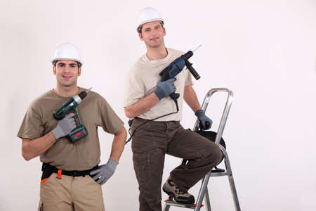 electric drill: Workmen holding their electric screwdrivers Stock Photo