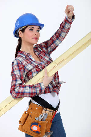 A female carpenter pointing at something. photo