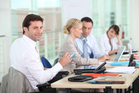 Businessman smiling to camera colleagues in background Stock Photo - 11049531