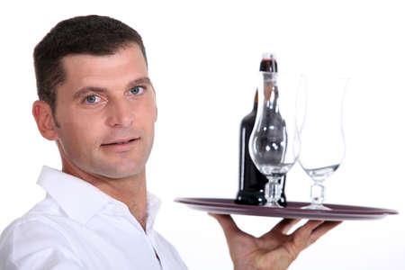 Waiter serving a bottle of beer photo