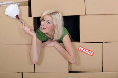 removals: Woman with a feather duster surrounded by packing boxes Stock Photo