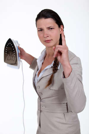 Annoyed woman with an iron photo