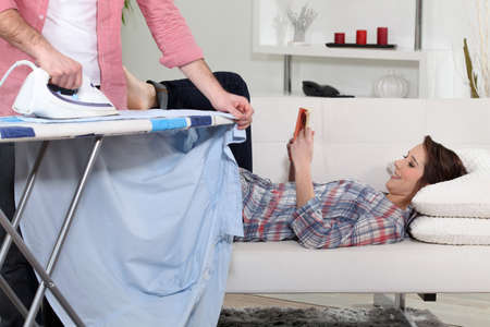 Woman lying on the couch reading while her boyfriend does the housework photo