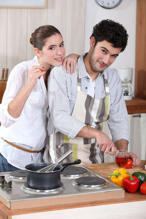 portrait of young man cooking in kitchen with girlfriend photo