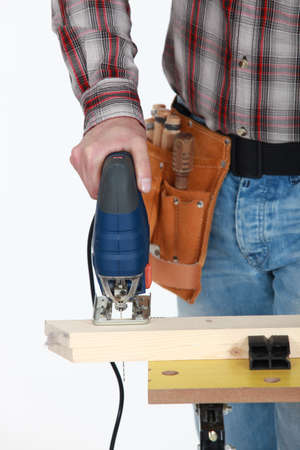 A cropped picture of a handyman using a jigsaw. photo