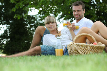 couple drinking orange juice in a park photo