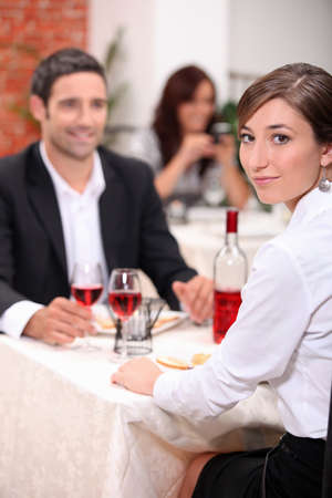couple at restaurant with woman turned to camera photo