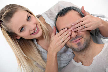covering eyes: woman surprising her boyfriend