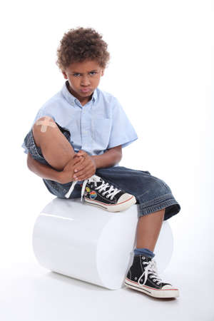 Little boy with a plaster on his knee photo