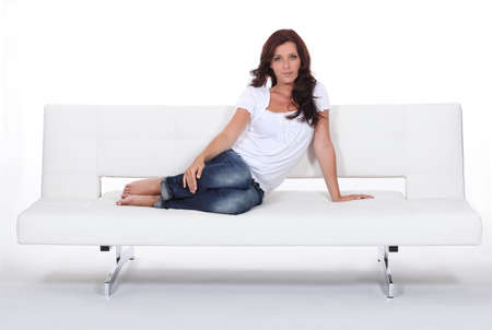 Attractive woman sitting with her feet up on a modern white sofa Stock Photo - 11049388