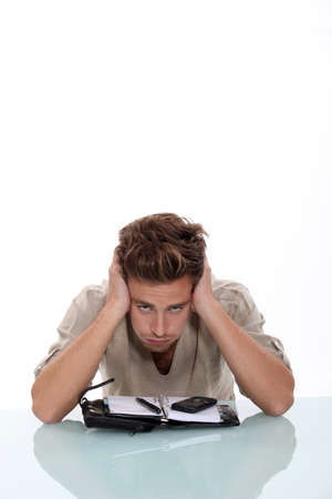 exasperated: Troubled young man exasperated with his diary