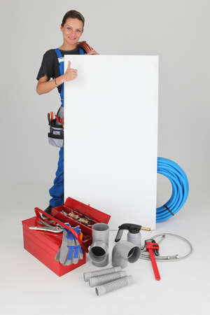 Woman with blank board, toolbox and thumbs up photo