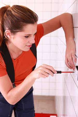 electric utility: Female electrician installing a wall socket