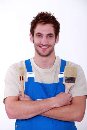 Young decorator holding two different paintbrushes photo