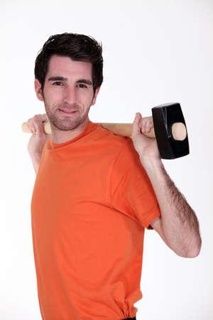 sledgehammer: Man carrying sledge-hammer over shoulder