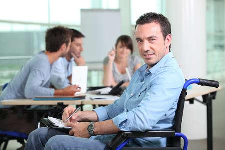 discapacidad: Empleado de oficina en una silla de ruedas con colegas en el fondo