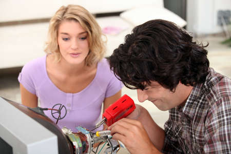 Couple repairing television Stock Photo