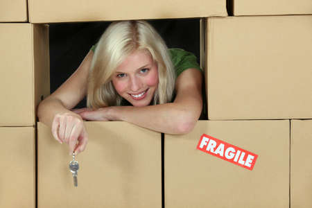 relocating: Woman surrounded by cardboard boxes Stock Photo