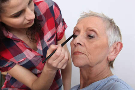 Woman applying makeup to an older lady photo