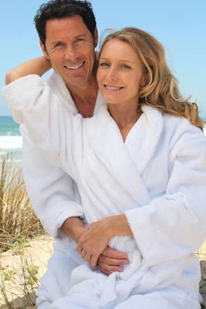 Portrait of couple on dunes in towelling robes photo