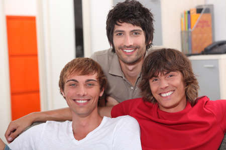 Three smiling lads sitting on a sofa Stock Photo - 11175997